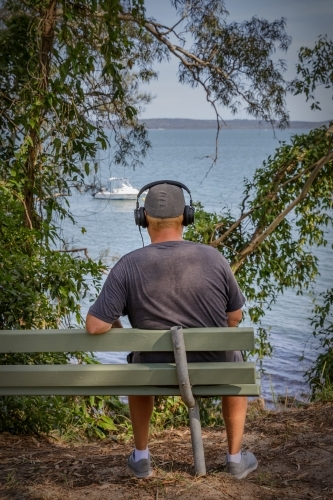 Rear view of young man wearing headphones, sitting on bench seat, looking out at sea view