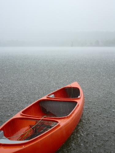 Red canoe sits idle on grey rainswept lake.