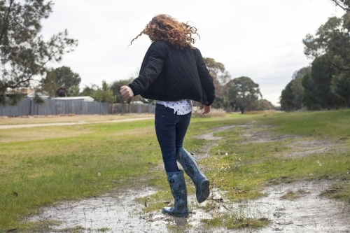 Red haired girl splashing in puddles in gumboots on a rainy winter day.