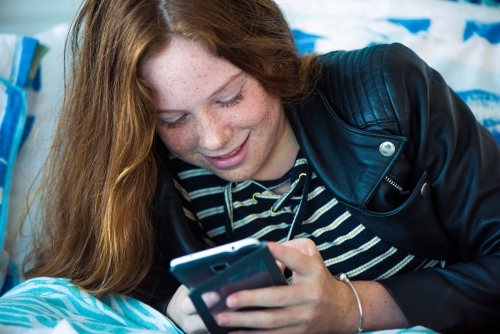 Red haired teenager girl lying on her bed while playing on her phone.