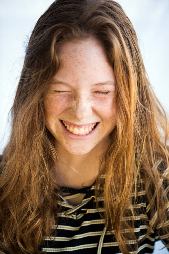 Red haired teenager screwing up face laughing