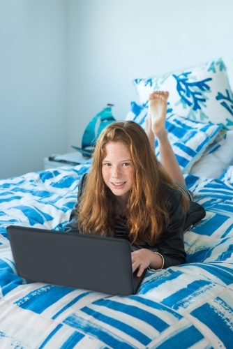Red haired teenager working on the computer while lying on the bed.