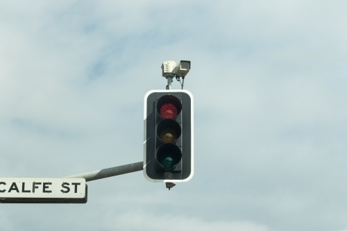 Red light speed camera mounted on traffic lights and  street sign