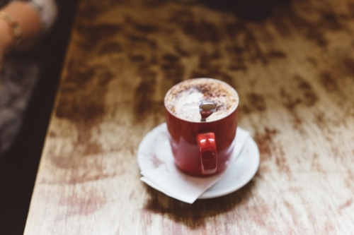 Red mug of coffee on a wooden table