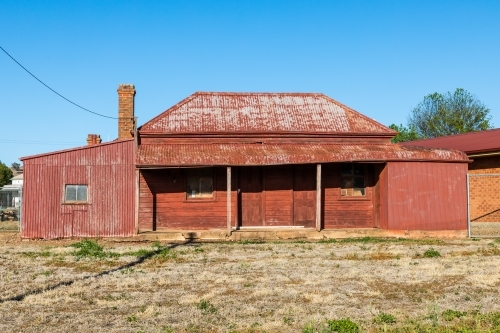 Red rusted, sun drenched, rundown, country house against a clear blue sky