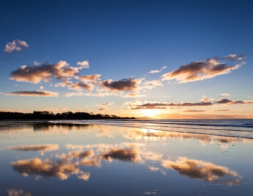 Reflection of sunset sky in wet sand at beach