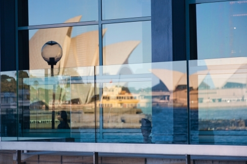 Reflection of the opera house and sydney ferry in windows at circular quay, sydney