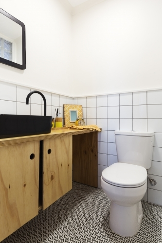 Renovated powder room with decorative floor tiles and black vanity