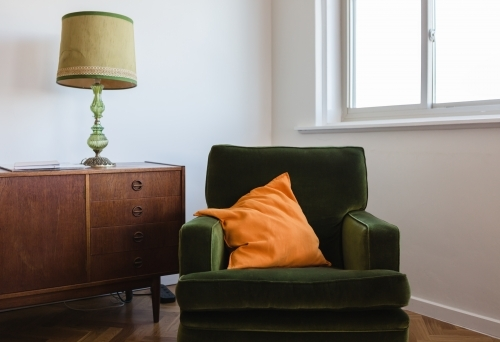 Retro living room furniture of a green velvet armchair and mid century buffet