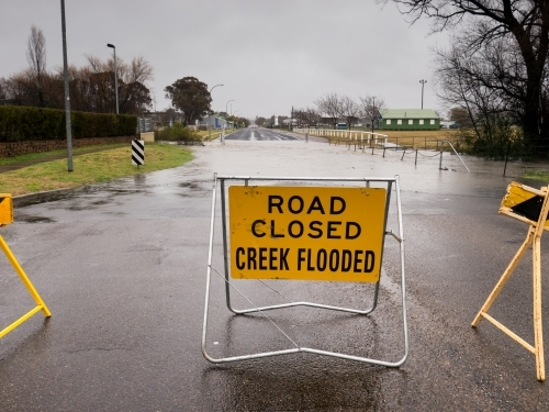 """ROAD CLOSED CREEK FLOODED"" sign on underwater bitumen road"