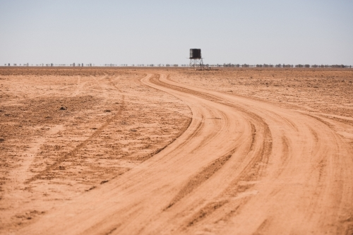 Road leading to a tank in a barren paddock