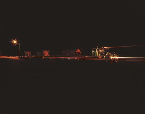 Road train at night with light trails