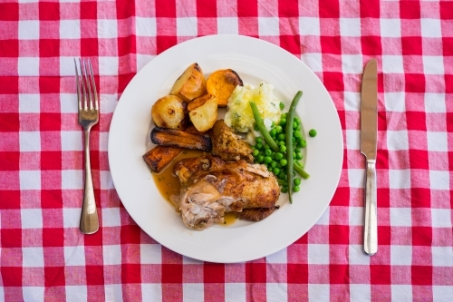 Roast chicken dinner on checkered tablecloth