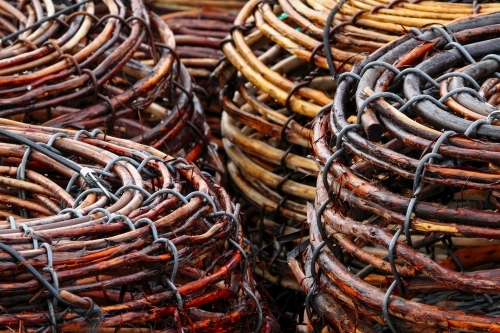 Woven cane Rock Lobster Pots stacked on the deck of a fishing boat.
