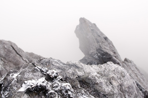 Rocks covered in patchy snow and mist