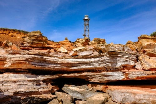 Rocky coastline with lighthouse tower against blue sky