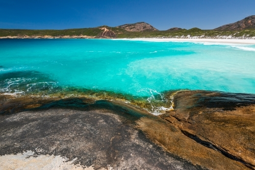 Rocky foreground with clear water and sweeping view of coastline with white sand beach