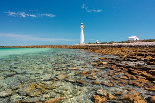 rocky shore with lighthouse and outbuildings under blue sky