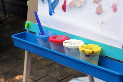 Row of paint pots on easel tray