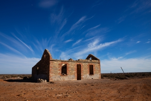 ruin under blue sky with wispy clouds