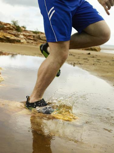 Running through a puddle and splashing at the beach