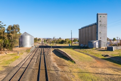 Rural industrial scene with railway lines, rail siding and factory silos