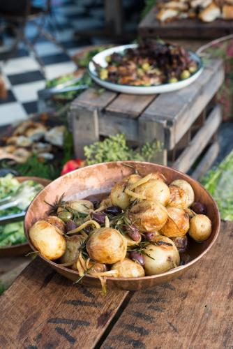 Rustic potato and olive dish on wooden table