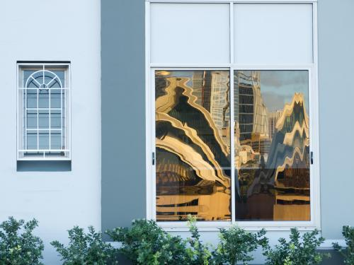 Sails of Sydney Opera House distorted and reflected in window