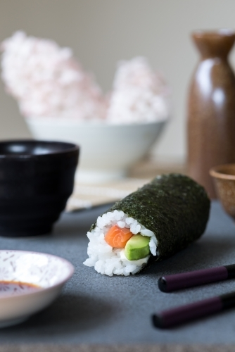 Salmon and avocado sushi roll with green tea and sake