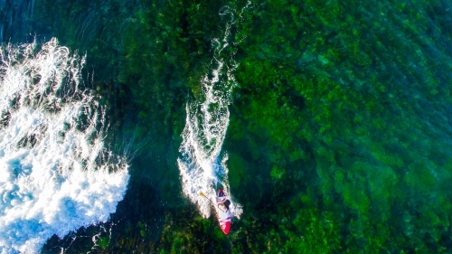 Aerial view of man riding a SUP standup paddle board at Sandon Point