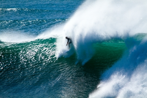 A male surfer in his late twenties surfing a large powerful wave at Sandon Point, NSW