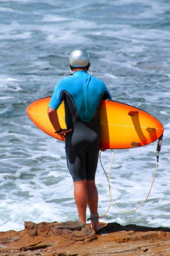 A middle aged male surfer in hemet holds his orange surfboard and observes the surf from shore
