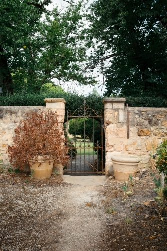 Sandstone wall with iron gate leading to green garden