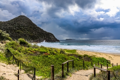 Sandy track leading to beach against mountain and cloudy sky