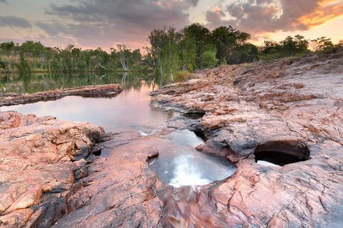 Water hole in rocky outcrop at sunset