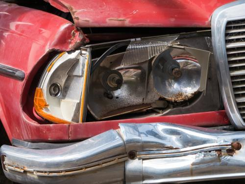 Broken headlight on a red car