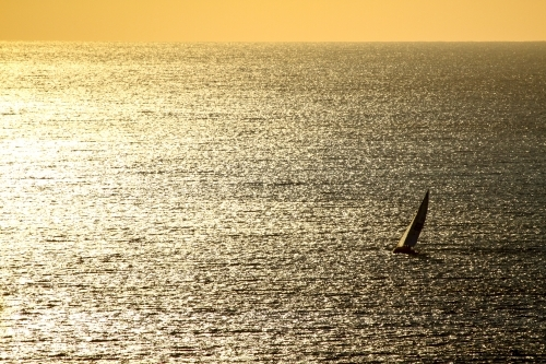 A lone yacht sailing on a vast shimmering ocean at sunrise