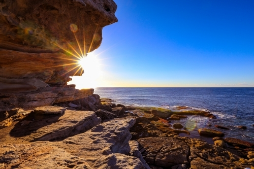 Scenic view of sea against blue sky on rocky coastline
