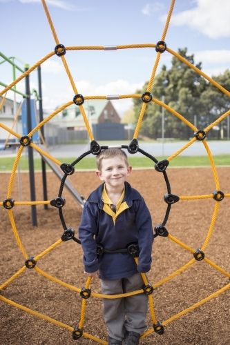 School age boy in centre of climbing net at playground
