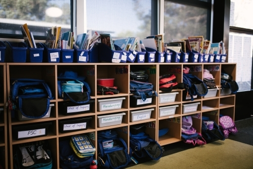 School bags and supplies on shelves in a classroom