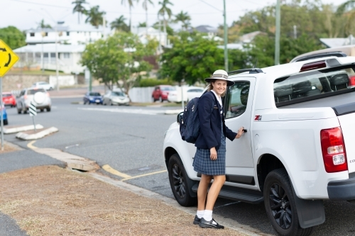 Schoolgirl in uniform about to open car door in street