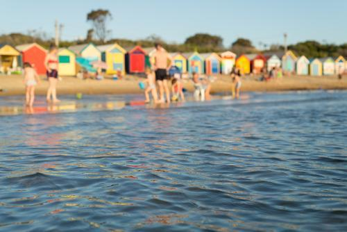 Selective focus of the ocean with colourful bathing boxes in the background