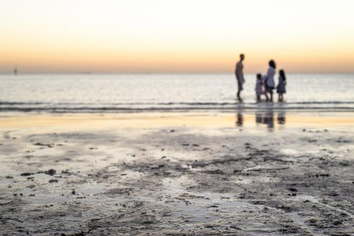Selective focus of the beach with a family standing in the ocean at dusk