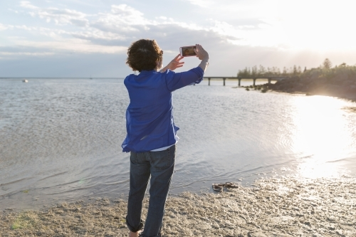 Senior woman taking phone photo on shoreline