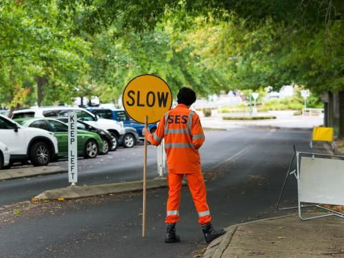 "SES Volunteer in an orange suit holding a ""SLOW"" sign"