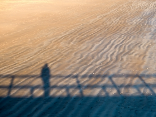 Shadow of a person, leaning on a rail, on a rippled beach sand pattern