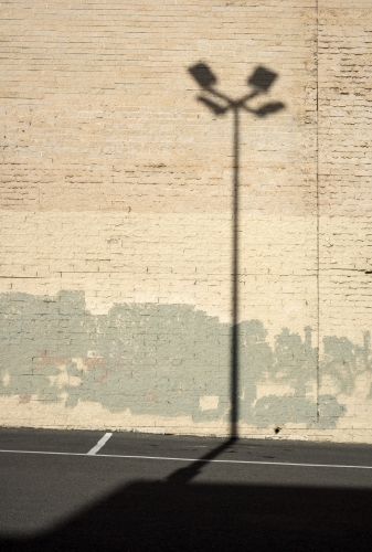 Shadow of a street lamp against a light brick wall