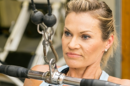 Close up of a woman pulling down on a weights machine