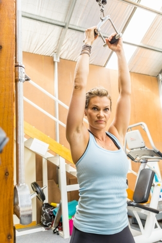 A fit woman with raised arms exercising on a weights machine