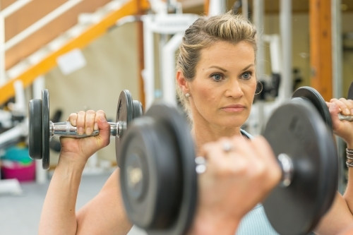 A woman lifting weights in a gym mirror